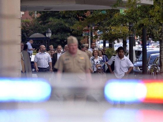 Zaměstnanci amerického vojenského námořnictva ve Washingtonu opouštějí budovu.