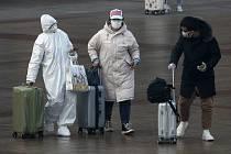 Cestující v ochranných maskách na nádraží v Pekingu