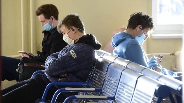 Cestující s rouškami v čekárně.