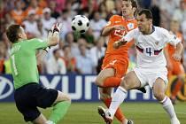 Ruský brankář Igor Akinfejev chytá míč před dotírajícím Nizozemcem Rafaelem van der Vaartem, asistuje mu obránce Sergej Ignaševič.
