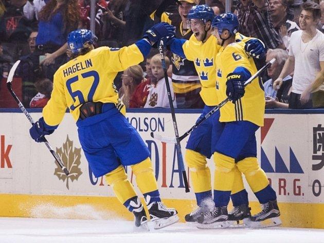 Hokejisté Švédska (zleva) Victor Hedman, Carl Hagelin a Anton Stralman se radují z gólu proti Rusku.