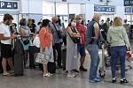 Cestující čekají na odbavení 1. července 2020 v hale Letiště Václava Havla v Praze