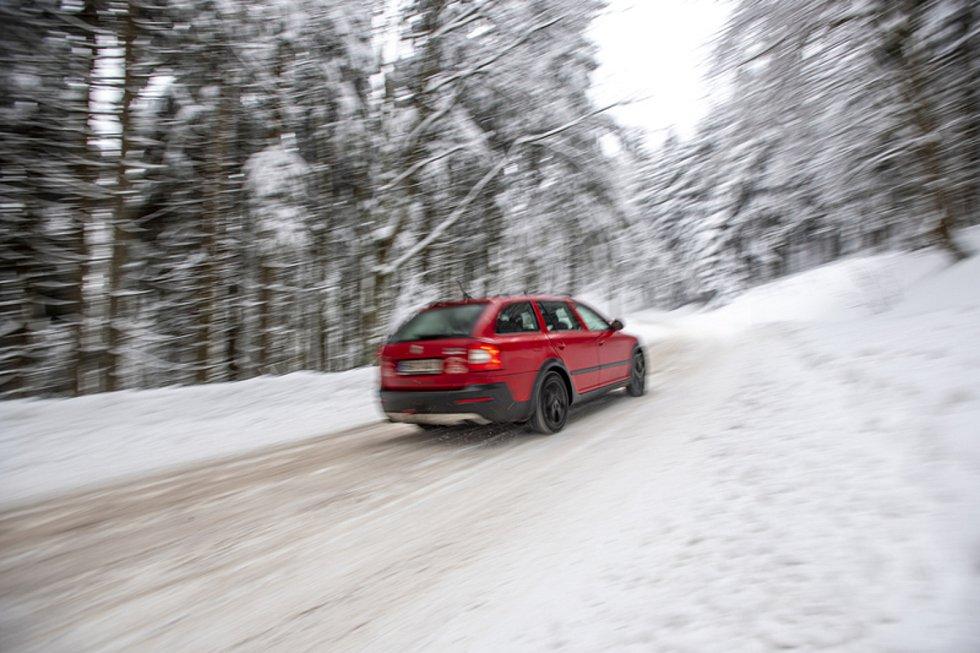 Automobil projíždí po zasněžené silnici. Ilustrační foto