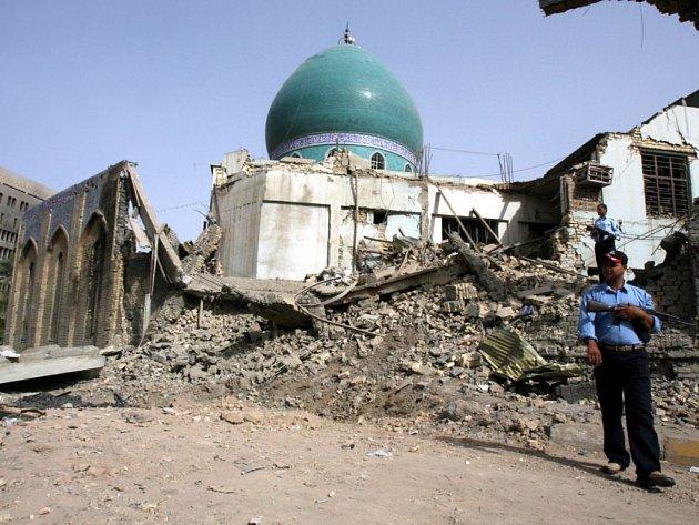 Policista hlídá poškozenou mešitu v Bagdádu.