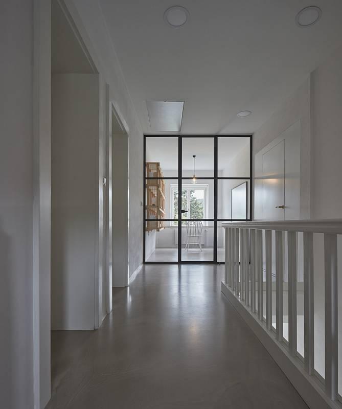 Netradiční skleněná stěna v první patře vymezuje prostor pro pracovnu.