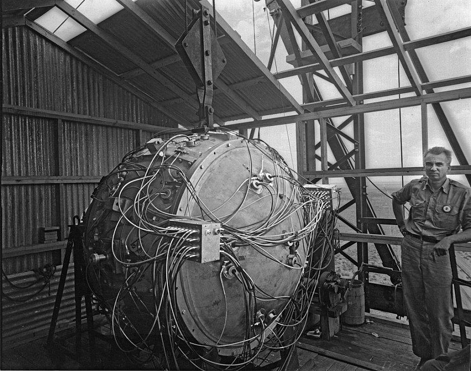 Norris Bradbury, vedoucí skupiny pro sestavení bomby, stojí vedle sestaveného gadgetu na vrcholu testovací věže