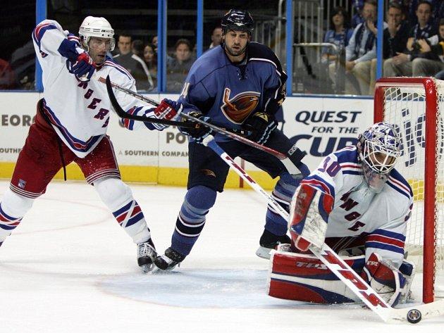 Brankář New York Rangers Henrik Lundqvist uklízí puk zatímco se jeho týmový kolega Matt Cullen snaží zastavit Shana Hnidyho z Atlanty.