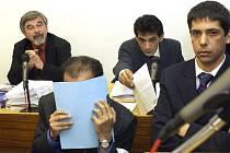 Listem papíru kryje svoji tvář člen katarské královské rodiny Hámid bin Abdal Sání u Obvodního soudu pro Prahu 2.