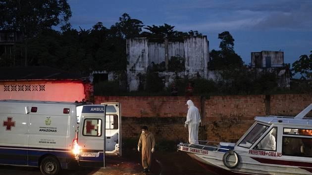 Zdravotník na lodi, která přivezla pacienta s covidem-19, sleduje jeho přesun do sanitky v brazilském přístavu Manacapuru.