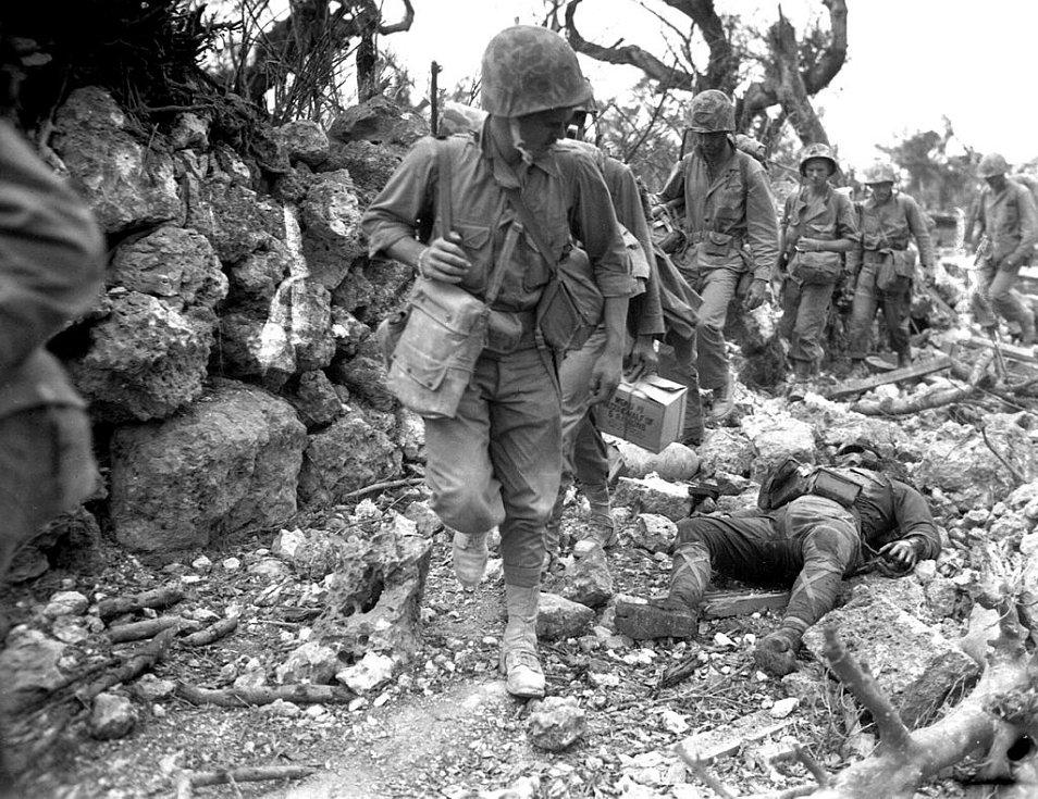 Příslušníci americké námořní pěchoty překračují mrtvá těla japonských vojáků ve zničené vesnici