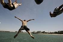 Muži se ochlazují koupáním v moři. Teplota vzduchu v Austrálii dosahuje teploty 43 stupňů Celsia. Vedra už zabila na 22 osob.