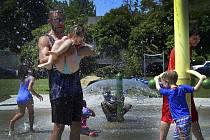 Lidé ve městě Olympia se ochlazují ve fontáně v parku během horkého dne