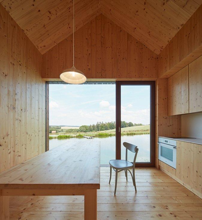 Skrze minimální zádveří lze vstoupit do ústřední místnosti, obytné kuchyně, jejíž součástí je i nevelký podkrovní prostor určený pro spaní dětí. Kuchyně nabízí nádherný výhled na vodní hladinu, stejně jako ložnice a obývák
