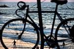 Lidé na poloprázdné pláži v Tel Avivu při západu slunce