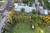 Příbuzní a přátelé pohřbívají rakev s ostatky Diega Maradony (vpravo). Vlevo nahoře policie zadržuje fanoušky před hřbitovem Jardín Bella Vista na předměstí Buenos Aires.