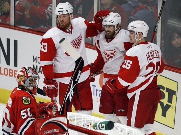 Hokejisté Detroitu se radují z gólu na ledě Chicaga. Zleva v bíločerveném dresu Johan Franzén, autor branky Henrik Zetterberg a Jiří Hudler. V popředí smutný gólman Blackhawks Corey Crawford.