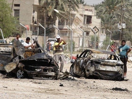 Civilisté prohlížejí trosky aut po výbuchu v Bagdádu.