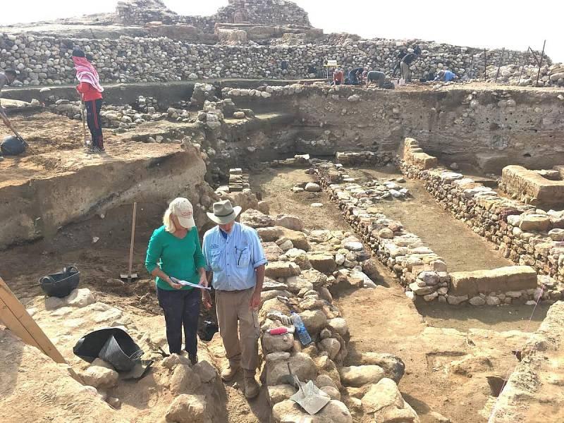 Badatelé zkoumají ruiny starověkého města, přičemž uprostřed odhalených zdí nacházejí stopy dávné destrukce