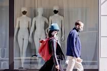 Lidé v rouškách prochází kolem výlohy obchodu v Berlíně 6. dubna 2020