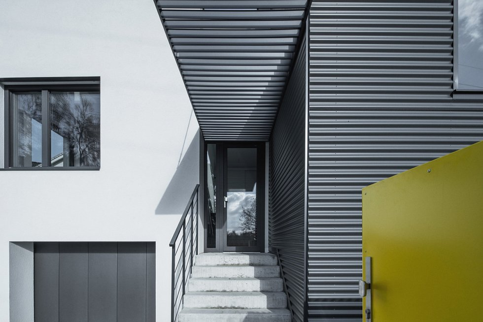 Nárožní část objektu, kde nástavba nahradila podkroví, o sobě dává vědět netradiční fasádou z jemně profilovaného šedého plechu.