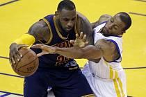 LeBron James z Clevelandu (vlevo) se snaží prosadit přes bránícího Andreho Iguodalu z Golden State.