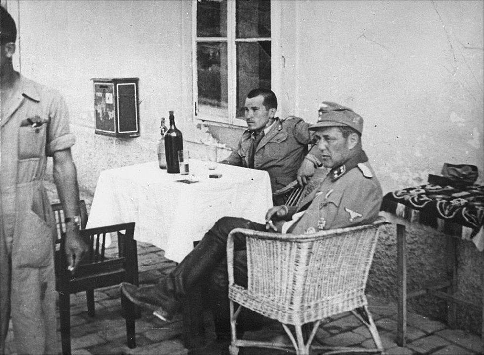 Vjekoslav Luburić sedící za stolem ve společnosti německého důstojníka