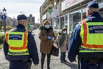 Maďarští policisté na ulici ve městě Békéscsaba kontrolují dodržování nařízení vydaných v souvislosti s koronavirovou epidemií.