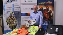Milan Baxa ukazuje chytré pracovní oděvy a v ruce má prototyp ortézy pro elektroterapii.