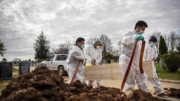 Hrobníci v ochranných oblecích nesou rakev s ostatky člověka, který zřejmě podlehl nemoci covid-19. Na snímku z 21. dubna 2020 ho jdou pohřbít bez přítomnosti rodiny na hřbitov Mount Richmond v newyorské čtvrti Staten Island.