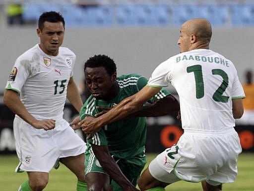 Nigerijec Chinedu Obasi (uprostřed) mezi dvěma bránícími hráči Alžírska Karim Zianim (vlevo) a Reda Baabouchem.