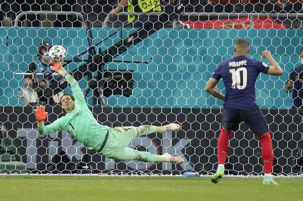 Švýcarský brankář Yann Sommer (vlevo) chytá v rozstřelu osmifinále ME penaltu Kyliana Mbappého.