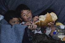 Děti migrantů jedí chleba v řecké vesnici Skala Sikaminias nna ostrově Lesbos