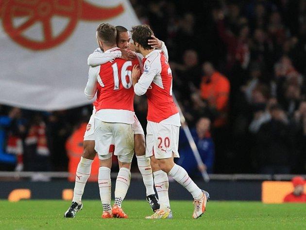Theo Walcott Z Arsenalu (uprostřed) se raduje se spoluhráči z gólu proti Manchesteru City.