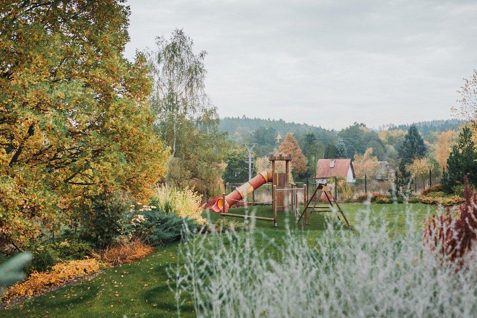 Vzadní části zahrady se vydovádějí děti. Kromě extra dlouhé apoměrně strmé skluzavky si tu mohou užívat houpačky, hrát si vevěži skrytou klouzačkou nebo trénovat balanc nadalších herních prvcích. Kdispozici je jim itrampolína zadomem.