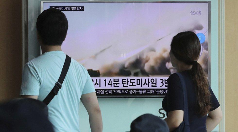 Lidé sledují na železniční stanici v jihokorejském Soulu záběry z testu balistických raket, který provedla Severní Korea