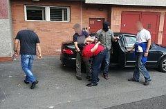 Policisté předvádějí zadrženého mladíka na služebnu