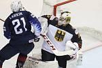 Americký hokejista Dylan Larkin (vlevo) překonává německého brankáře Matthiase Niederbergera.
