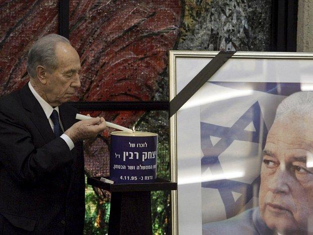 Iraelský prezident Šimon Peres zapaluje svíčku před obrazem Jicchaka Rabina.