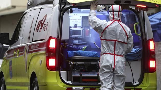 Zdravotník dezinfikuje sanitku v Jižní Koreji