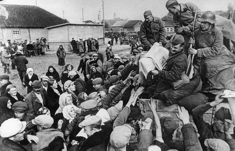 Vojáci Rudé armády rozdávají polským rolníkům sovětské propagandistické noviny v Sověty okupované části Polska