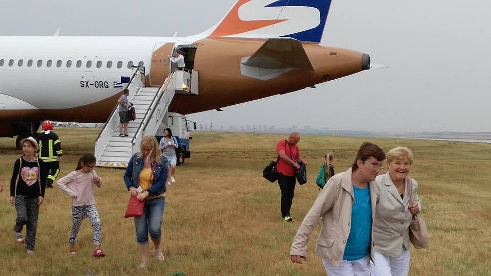 Letadlo společnosti Travel Service na trávě mimo přistávací dráhu