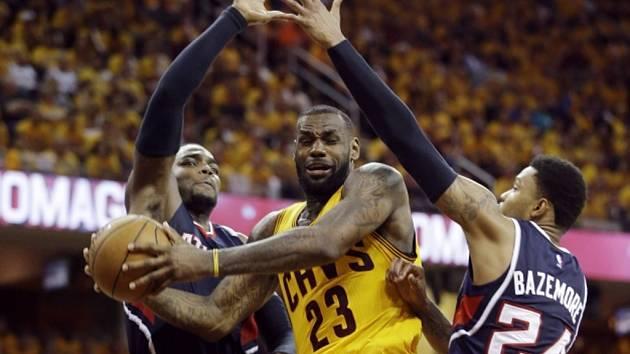LeBron James z Clevelandu (uprostřed) se prosazuje přes hráče Atlanty.