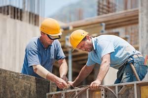 Stavební dělníci spolupracující při instalaci cementových bednění rámů.