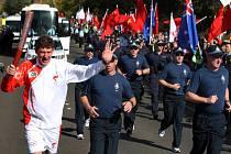 Australská policie doprovází běžce s pochodní. Čínská ostraha v modrých teplácích musela ustoupit.