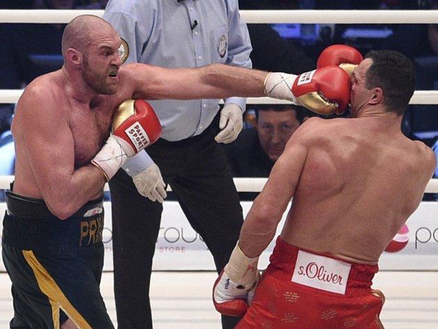 Tyson Fury (vlevo) a Vladimir Kličko v bitvě o mistrovské pásy organizací WBA, WBO, IBO a IBF.