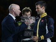 Tenisová legenda Andre Agassi (vlevo) předává Novaku Djokovičovi trofej pro vítěze Australian Open.