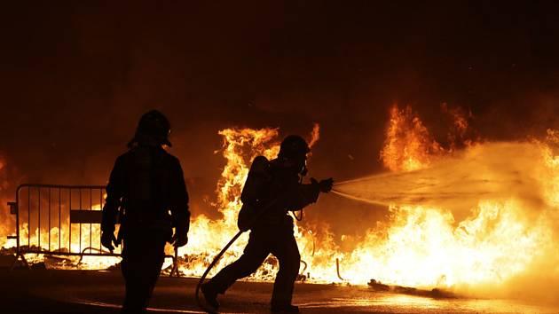 Hasiči likvidují na snímku z 18. října 2019 požár v centru Barcelony, kde demonstranti zapálili barikády.