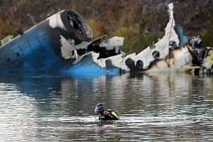 Jeden ze záchranářů hledá ve Volze ostatky cestujících, kteří zahynuli při cestě z Jaroslavle do Minsku.