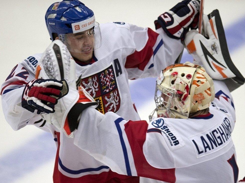Čeští hokejisté Dominik Simon (vlevo) a brankář Marek Langhammer se radují z vítězství nad Kanadou.