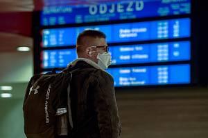 Muž s respirátorem stojí ve vestibulu Hlavního nádraží v Praze na snímku z 16. března 2020. Vláda zakázala volný pohyb lidí s výjimkou cest do zaměstnání, nezbytných cest za rodinou, pro základní životní potřeby nebo k lékaři.
